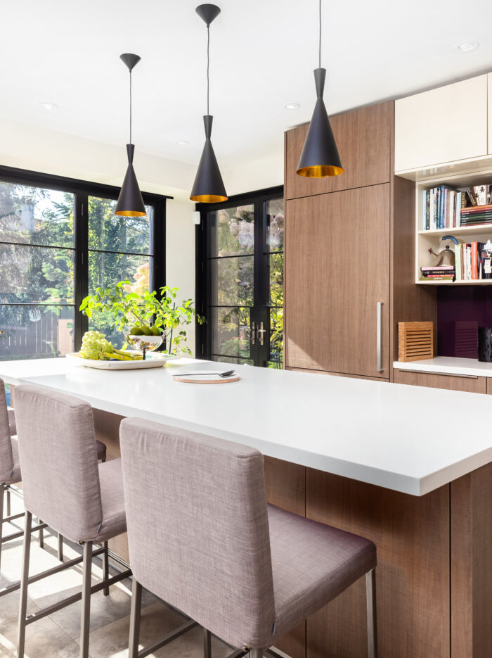 the interior of a beautiful kitchen. A breakfast bar is in frame with four chairs