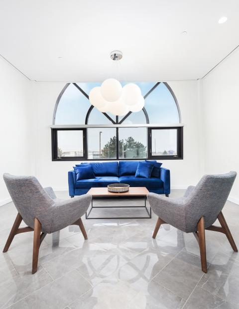 two chairs rest symmetrically in front of a royal blue couch